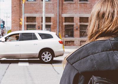 Girl walking across the street by a car